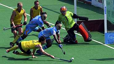 Australia's Trent Mitton (12) hits a goal against India during their men's field hockey final match