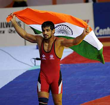 Sushil Kumar with the Indian flag after winning a gold medal