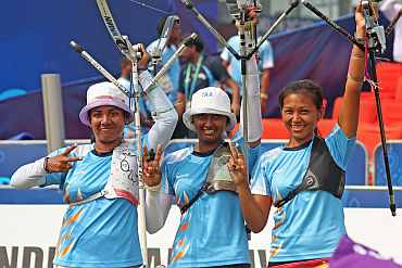 India's Dola Bannerjee, Deepika Kumari and Bombayla Devi celebrate after winning gold