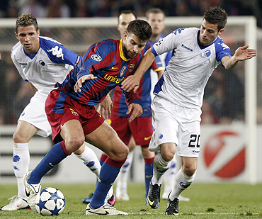 Barcelona's Gerard Pique (centre) vies for possession with FC Copenhagen's Martin Vingaard and Claudemir (lef