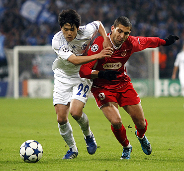 Schalke 04's Atsuto Uchida is challenged by Hapoel Tel Aviv's Etey Schechter (right)