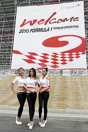 Grid girls pose in the paddock after the qualifying session of the South Korean F1 Grand Prix in Yeongam on Saturday