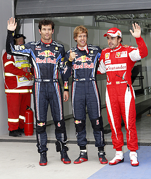 Red Bull's Sebastian Vettel celebrates winning pole position as he is flanked by teammate Mark Webber (left) and Ferrari's Fernando Alonso after qualifying at the Korea International Circuit in Yeongam on Saturday