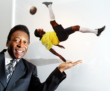 Pele stands next to a photograph of him at a photo exhibition