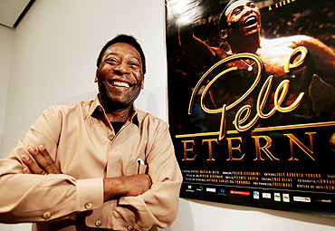Pele poses next to a poster of documentary film 'Pele Forever' at New York's Museum of Modern Art