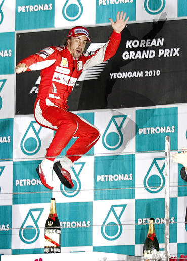 Ferrari Formula One driver Fernando Alonso of Spain jumps as he celebrates on the podium after winning the South Korean F1 Grand Prix