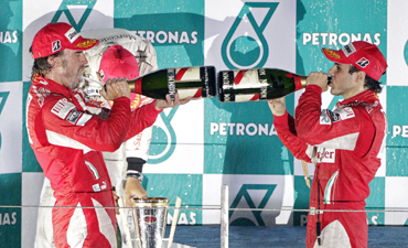 Ferrari Formula One driver Fernando Alonso of Spain (L) and his teammate Felipe Massa of Brazil spray champagne as they celebrate on the podium after Alonso won the South Korean F1 Grand Prix