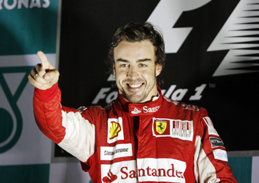 Ferrari Formula One driver Fernando Alonso of Spain points as he celebrates on the podium after winning the South Korean F1 Grand Prix