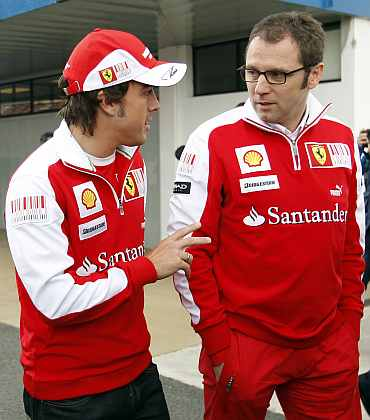 Ferrari's Fernando Alonso talks with team principal Stefano Domenicali in the paddock area