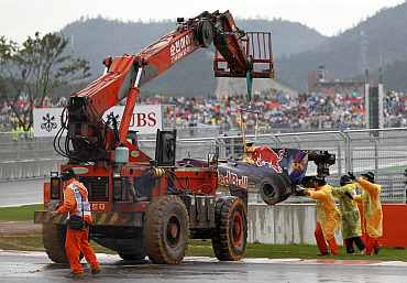 A crane lifts the car of Red Bull driver Mark Webber after he crashed out of the South Korean F1 Grand Prix