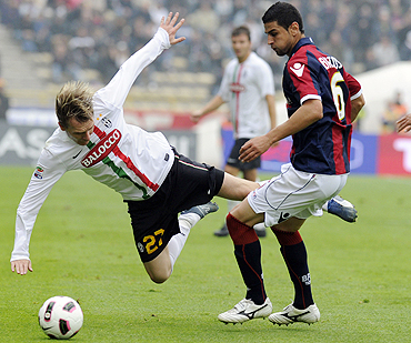Juventus' Milos Krasic (left) and Miguel Britos of Bologna vie for possession during their Serie A match on Sunday