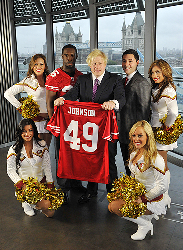 London's Mayor Boris Johnson (centre) poses with US NFL football cornerback for the San Francisco 49ers, Shawntee Spencer, club owner Jed York and cheerleaders from the balcony at City Hall in London on Tuesday