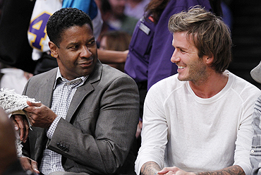 Actor Denzel Washington (left) and English footballer star David Beckham chat during the NBA game in Los Angeles, California, on Tuesday