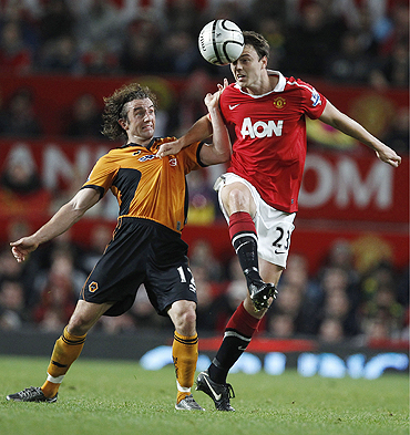 Manchester United's Jonny Evans (right) challenges Wolverhampton Wanderers' Stephen Hunt