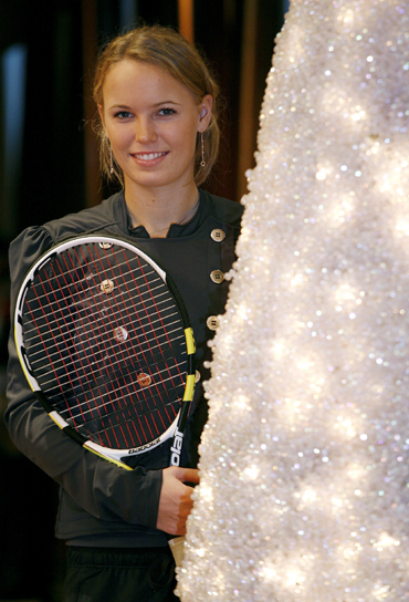 Caroline Wozniacki poses beside a Christmas tree after a news conference introducing players for the upcoming Tennis Classic in Hong Kong