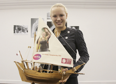 Caroline Wozniacki holds small souvenir boats during their WTA Tour Championships tennis match in Doha