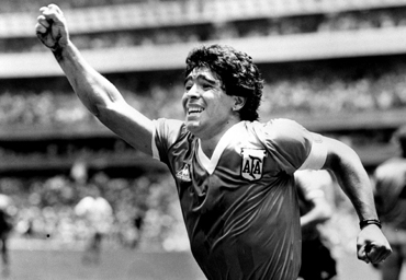 Diego Maradona raises his arm after scoring the winning goal against England