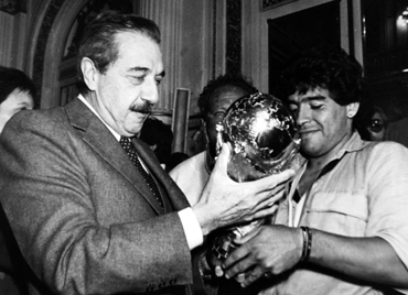 Diego Maradona (R), captain for the 1986 World Cup-winning  squad, hands the trophy to then Argentine President Raul Alfonsin in Buenos Aires