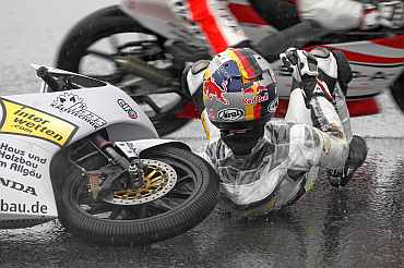Honda 125 cc rider Marcel Schrotter of Germany falls during the second free practice session of the Portuguese Grand Prix in Estoril