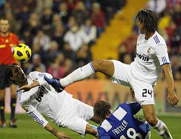 Real Madrid's Esteban Granero (R) kicks the ball past Hercules' Matias Fritzler