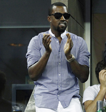 Musician Kanye West cheers from a private box