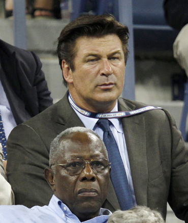 Baseball great Hank Aaron sits in front of actor Alex Baldwin as they watch Kim Clijsters of Belgium play Samantha Stosur of Australia