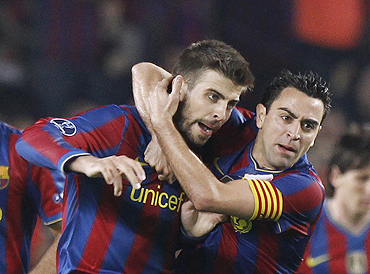 Barcelona's Xavi (right) and teammate Gerrard Pique