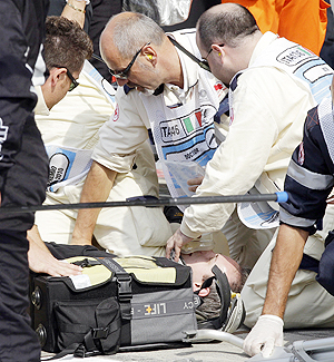 A Hispania Racing Team radio engineer receives first aid after being hit by a wheel of Hispania driver Sakon Yamamoto during the Italian F1 Grand Prix on Sunday