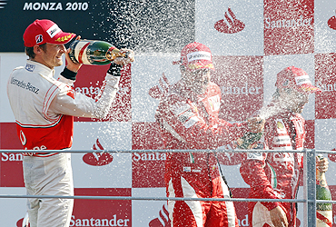 Jenson Button (left), Fernando Alonso and Felipe Massa (right) celebrate on the podium