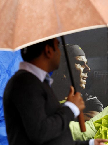 A fan walks past a poster of Rafael Nadal during a rain delay before the start of the men's final at the US Open