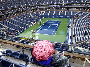 Fans sit in the rain inside the Arthur Ashe Stadium during the rain delay