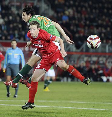 Twente's Wout Brama (red) challenges Werder Bremen's Claudio Pizarro