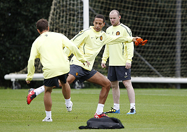 Manchester United's Wayne Rooney (right) watches teammates Rio Ferdinand (centre) and Michael Owen during a training session at the Carrington training complex in Manchester on Monday
