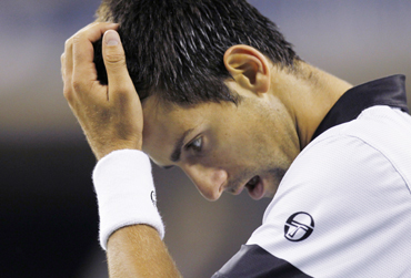 Novak Djokovic of Serbia reacts to losing a point during his match against Rafael Nadal of Spain