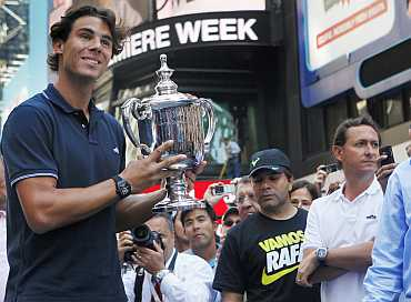 Rafael Nadal of Spain, winner of the 2010 US Open, poses with the trophy at Times Square in New York