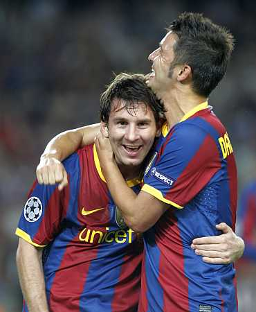 Lionel Messi celebrates with David Villa after scoring a goal