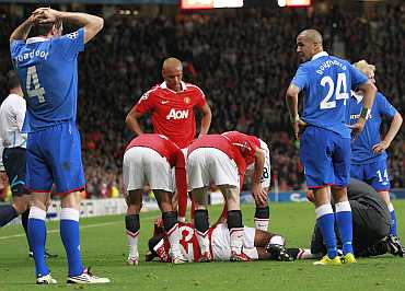 Manchester United players comfort injured team mate Valencia as Rangers' Broadfoot, Bougherra and Naismith look on