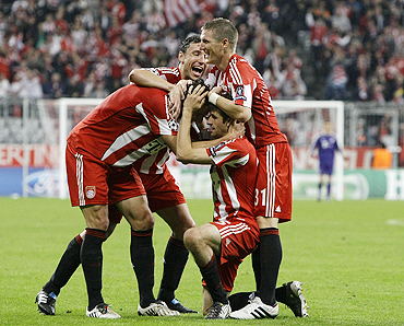 Bayern Munich's Thomas Mueller (kneeling) celebrates with teammates after scoring against AS Roma