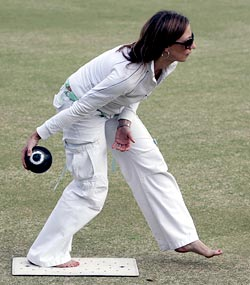 Yvonne Derksema plays a shot during a game of barefoot lawn bowls at a bowling club in Manly in Sydney