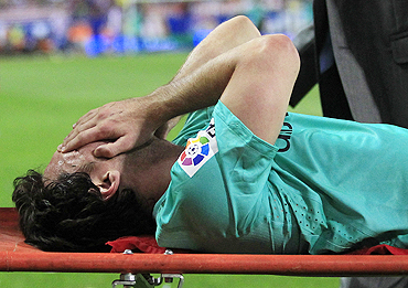 Lionel Messi grimaces as he is led out on a stretcher after getting injured