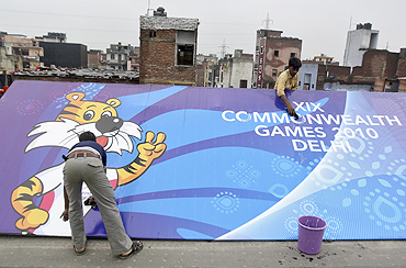 Workers clean a billboard outside the Commonwealth Games athletes village in New Delhi