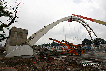 A crane removes waste from a collapsed pedestrian bridge outside the Jawaharlal Nehru Stadium in New Delhi