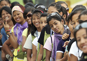 Volunteers wait in line as they wait to be checked at a security checkpoint before entering the Jawaharlal Nehru Stadium complex in New Delhi