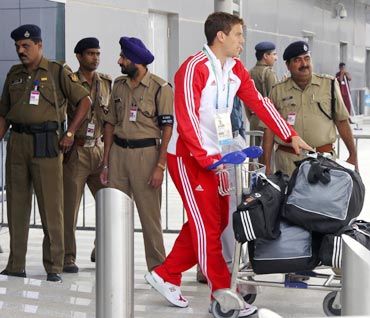 A member from England's team walks past Indian security personnel at the Delhi airport