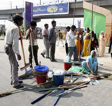 Workers prepare their brooms before entering the Games village