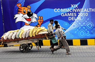 Labourers pull a handcart loaded with bricks and sand in front of boards advertising the Commonwealth Games.
