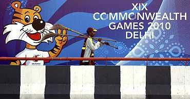 A man carries brooms in front of a board advertising the 2010 Commonwealth Games in New Delhi