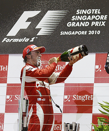Ferrari Formula One driver Fernando Alonso of Spain sprays champagne as he celebrates on the podium after winning the Singapore GP
