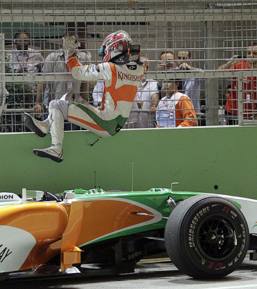 Force India's Vitantonio Liuzzi climbs off the track after retiring from the Singapore GP