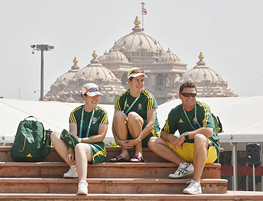 Australian athletes Lynsey Aromitage (left), Leif Selby (right) and Claire Duke sit inside the Commonwealth Games Village with the Akshardham temple in the background